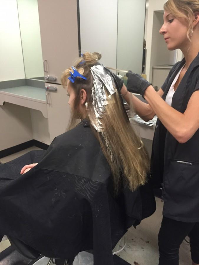 Natalie Murphy applying highlights to Grace Eait.