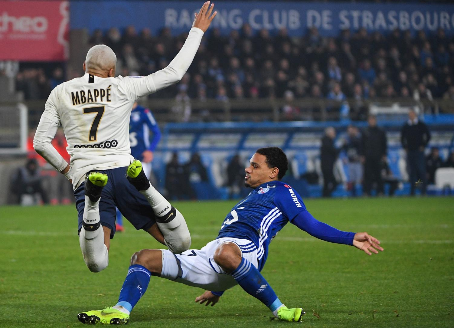 Paris Saint-Germain's French forward Kylian Mbappe (L) falls on the football as he vies for the ball with Strasbourg's French defender Kenny Lala (R)